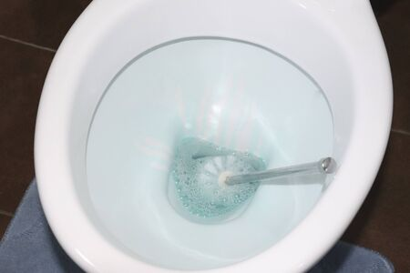 toilet close-up with disinfectant. the process of cleaning in the bathroom, the rest room,