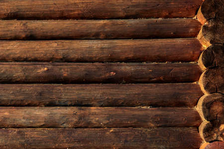 the wall of Russian national wooden house. Log Cabin Or Barn Unpainted Debarked Wall Textured Horizontal Background With Copy Space.