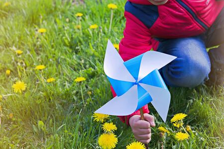 A boy is playing with a bright blue home-made paper toy weather vane in the garden among the grass. Childrens crafts, creativity, DIY. Summer concept Reklamní fotografie