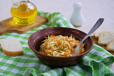 Coleslaw salad of fresh cabbage and carrots in a brown clay bowl on a light concrete background. Healthy food. Vegetarian recipes. Imagens