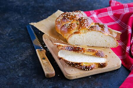 Homemade sliced challah, traditional wicker white bread on a wooden board on a black concrete background. Copyspace.