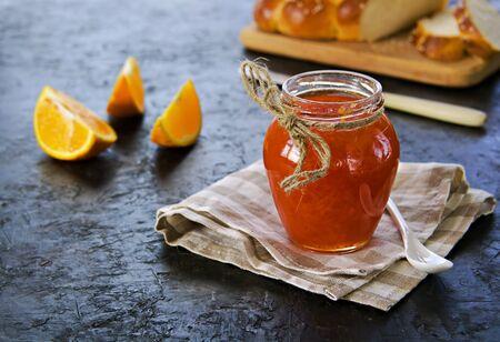 Carrot jam with orange in a glass jar on a black concrete background. Vegetable jams. Preservation, harvest. Imagens