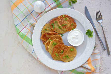 Traditional potato pancakes made from raw potatoes on a white plate on a light background concrete. Belorussian cuisine. Potato Recipes. Served with sour cream.