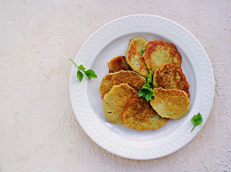 Traditional potato pancakes made from raw potatoes on a white plate on a light background concrete. Belorussian cuisine. Potato Recipes.