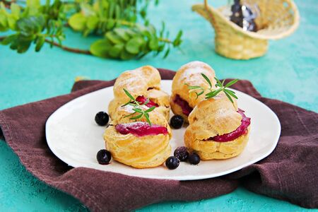 Dessert, choux pastry with cream of cream cheese and blackcurrant berry mousse on a white plate on a turquoise concrete background. Berry Cream Desserts recipe.