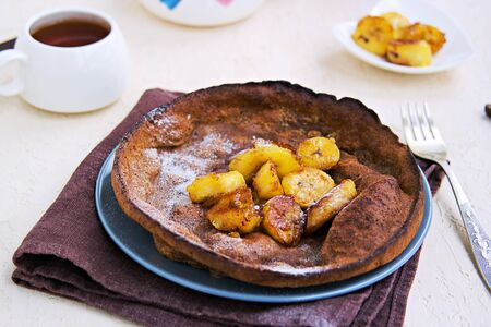 Chocolate Dutch Baby pancake with caramelized bananas on a gray plate on a light concrete background. Selective focus. American cuisine. Dessert for Valentine's Day