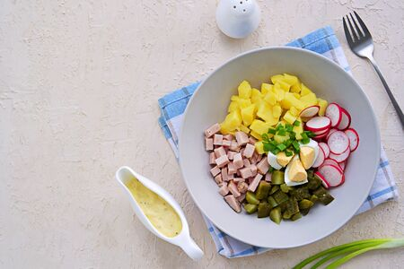 Potato salad with ham, fresh radish and pickled cucumber in a gray bowl on a light concrete background. American cuisine. Potato Recipes. Top view, copyspace 写真素材
