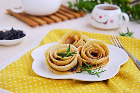 Pancakes, rolled up in the shape of a rose flower, on a white plate on a light concrete background. Pancake Day concept. Pancake Recipes. Served with plum jam 免版税图像