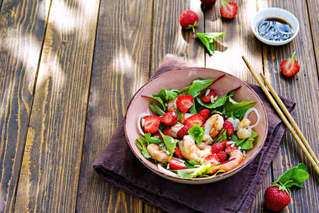 Salad with fresh strawberries, fried shrimp and young beet tops in a pink bowl on a wooden background. Recipes for salads with berries.