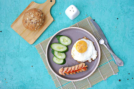 Breakfast, fried egg with sausage and slices of fresh cucumbers on a brown clay plate on a turquoise concrete background. Childrens breakfasts. School breakfast concept. Top view, copy space.