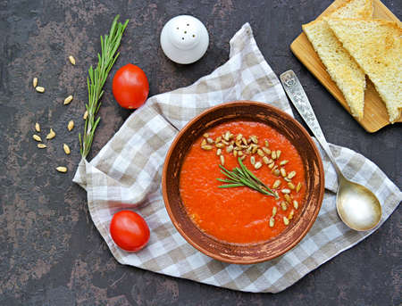 Cream soup of baked sweet pepper and tomato in a clay bowl on a brown concrete background. Served with dried white bread and sunflower seeds. Vegan recipes. Healthy food.