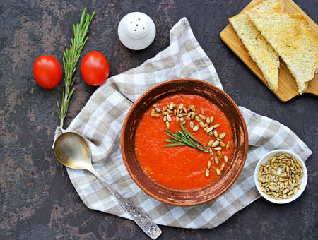 Cream soup of baked sweet pepper and tomato in a clay bowl on a brown concrete background. Served with dried white bread and sunflower seeds. Vegan recipes. Healthy food. Top view.