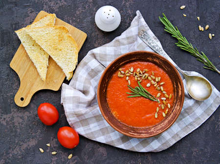 Cream soup of baked sweet pepper and tomato in a clay bowl on a brown concrete background. Served with dried white bread and sunflower seeds. Vegan recipes. Healthy food. Top view. Archivio Fotografico