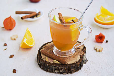 Apple cider with spices. Alcoholic or non-alcoholic hot drink made from fresh unfiltered apple juice with spices, apple slices and orange in a glass mug on a light concrete background. Stock Photo