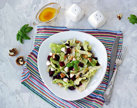 Green salad with boiled beetroot, feta and walnuts in a white plate on a gray concrete background. Seasoned with olive oil, grain mustard and vinegar. Healthy food. Top view. Stockfoto