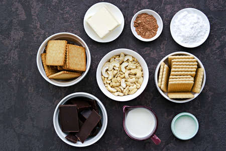 Ingredients for dessert, chocolate salami on a dark concrete background: sugar cookies, dark chocolate, croquet cookies, cream, sugar, cocoa, icing sugar, butter, cashew nuts. Dessert recipes.