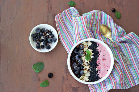Smoothie bowl based on mashed berries, banana and natural yogurt in a white bowl. Decorated with frozen blackcurrant, sliced almonds and black sesame seeds. Healthy dessert. Top view, copy space.