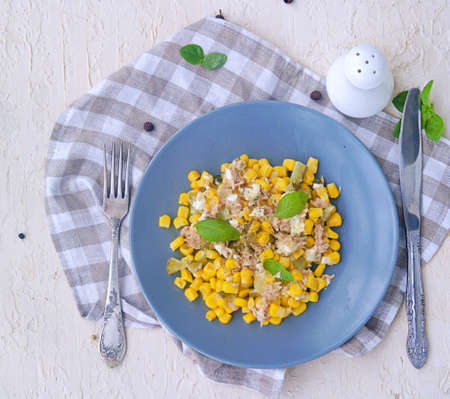 Salad with tuna, corn and pickled cucumber on a gray plate on a light concrete background. Tuna salad recipes. Top view. Фото со стока