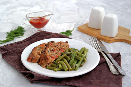 A meatloaf with mushrooms and red sweet pepper on a white plate with a garnish of fried green beans. Selective focus. Reklamní fotografie
