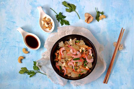 Refreshing salad with pomelo, shrimps, carrots and cashew nuts in a black bowl on a light blue background. Asian cuisine. Top view.