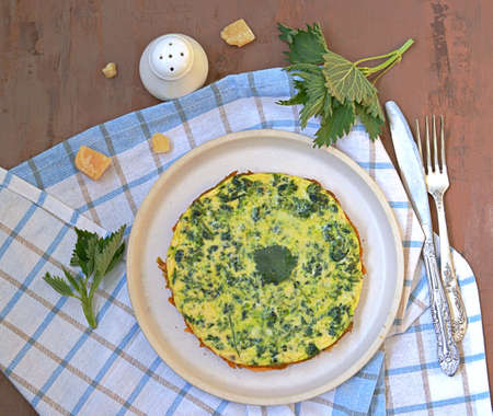 Breakfast, omelet with nettles on a white clay plate. Healthy food. Food from wild herbs. Top view, copy space.