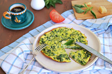 Breakfast, omelet with nettles on a white clay plate. Healthy food. Food from wild herbs.