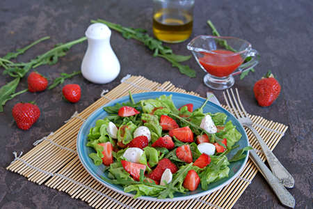 Salad with strawberries, arugula and mozzarella cheese on a dark brown background concrete. Healthy food.