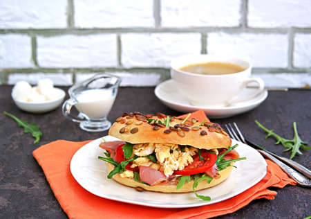 Breakfast, bagel with scramble egg, ham, arugula and vegetables on a white plate on a dark background.