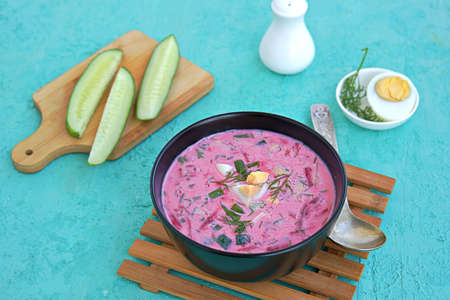 Cold beet soup with green onions, cucumber and dill on kefir or buttermilk in a black bowl on a turquoise background. Served with boiled egg. Lithuanian cuisine. Healthy food, diet. Copy space.