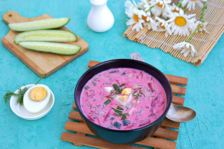 Cold beet soup with green onions, cucumber and dill on kefir or buttermilk in a black bowl on a turquoise background. Served with boiled egg. Lithuanian cuisine. Healthy food, diet. Reklamní fotografie