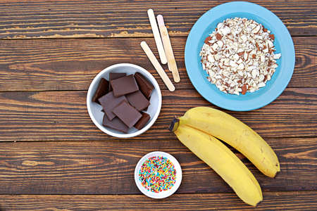 Ingredients for cooking frozen bananas in chocolate on wooden background. Top view, copy space. Reklamní fotografie