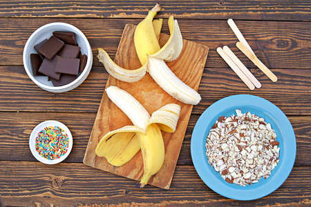 Ingredients for cooking frozen bananas in chocolate on wooden background: fresh bananas, chocolate, almond petals, sugar topping, sticks. Top view, copy space.