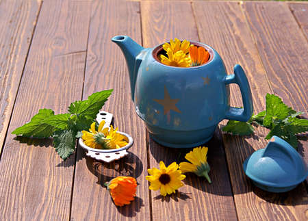 Cooking herbal tea in a blue clay teapot on a wooden background. Herbal teas and medicinal fees concept.