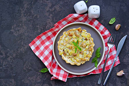 Portion mini tart with chicken, zucchini and fried onions on shortcrust pastry with sour cream and eggs filling on a clay plate on a dark concrete background. Savory pastry recipes. Zucchini recipes.