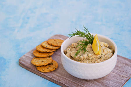 Appetizer, fish pate from mackerel, boiled eggs and onions in a white ceramic bowl on a blue concrete background. Served with savory crackers. Fish recipes.