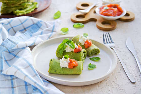 Spinach pancakes rolled up on a white plate on a light concrete background. Served with salted salmon and soft cheese. Spinach recipes.
