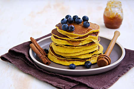 Pumpkin pancakes with blueberries and honey on a brown clay plate on a light concrete background. American cuisine. Thanksgiving day concept. Pumpkin recipes
