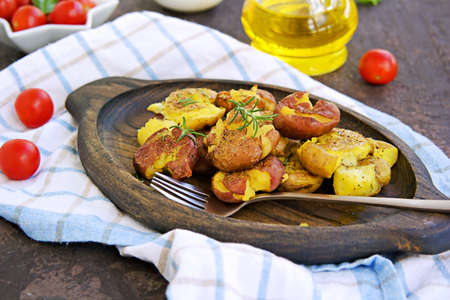 Crash Hot Potatoes, boiled potatoes in a peel, crushed and baked with olive oil and herbs on a wooden plate on a dark concrete background. Australian cuisine. Potato recipes. Thanksgiving day Imagens