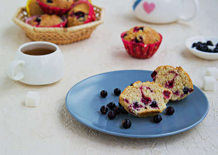 Sliced muffin with black currants on a blue plate on a light concrete background. American cuisine. Selective focus