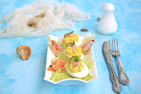 Cold appetizer, stuffed eggs with shrimps and pickled cucumber on a white dish. Stock Photo