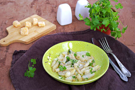Roasted Jerusalem artichoke with cheese and parsley on a green plate. Healthy food Stock fotó