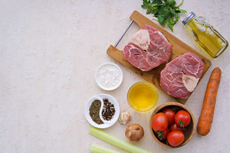 Ingredients for ossobuco, beef shank stew on a bone with carrots, tomatoes and celery on a light concrete background. Main meat dishes. Italian food. Copyspace. Top view