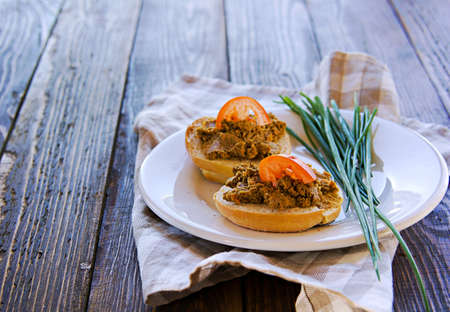 Homemade pate of pig or chicken liver on wheat buns on a white ceramic plate on brown wooden background. Pate recipes.