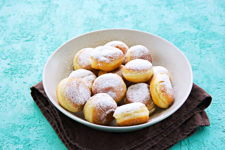 Mini donuts made from yeast dough sprinkled with icing sugar in a gray bowl on a turquoise concrete background. Deep-fried baking recipes. Hanukkah concept.