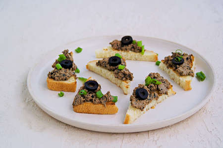 Chicken liver appetizer with salted olives on slices of toasted white bread on a light concrete plate. Offal recipes. Appetizer Recipes. Italian food.