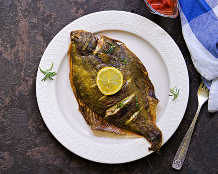 A whole flounder, baked in the oven, on a light plate on a brown concrete background. Fish recipes.