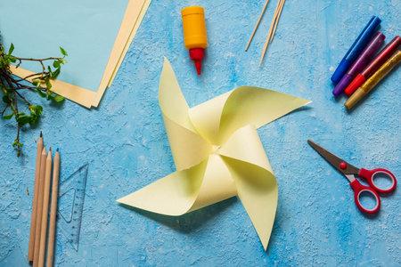 Step-by-step making of a paper weather vane by a child on a blue concrete background. Children's creativity, divas, crafts. Paper crafts Foto de archivo