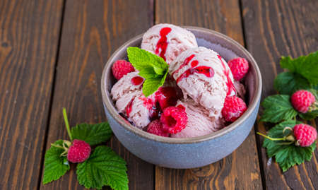 Balls of raspberry ice cream with fresh raspberries in a ceramic bowl on a brown wooden background. Ice cream recipes. Summer concept