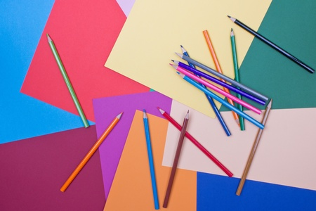 differently: background of differently colored papers and pencils