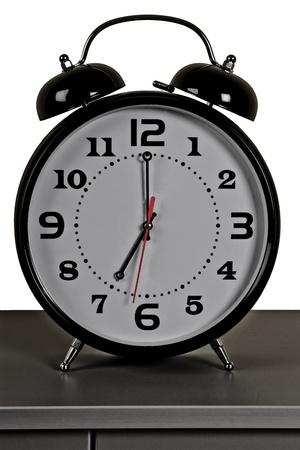 seven o'clock: black alarm clock: seven oclock